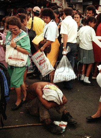 A homeless man lies in despair on a crowded street in San Salvador, El Salvador, Central America.