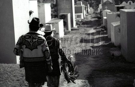 Two Guatemalan men dressed in traditional clothing visit their ancestors graves in a cemetery in Solola, Guatemala, Central America.
