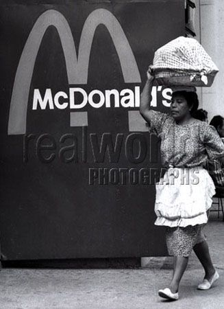 A woman carries a basket past a McDonalds sign in San Salvador, El Salvador, Central America, proof that money can be made for American interests even in the poorest of countries.