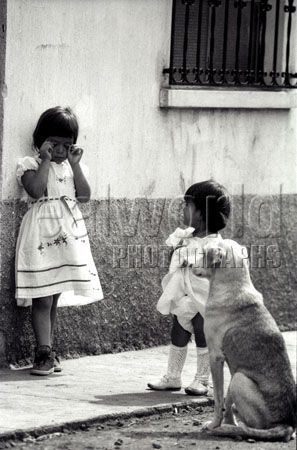 A toddler and pet dog try their best to console a sad girl in her Sunday dress. The three were spotted in an alley on the edge of Guatemala City, Central America.